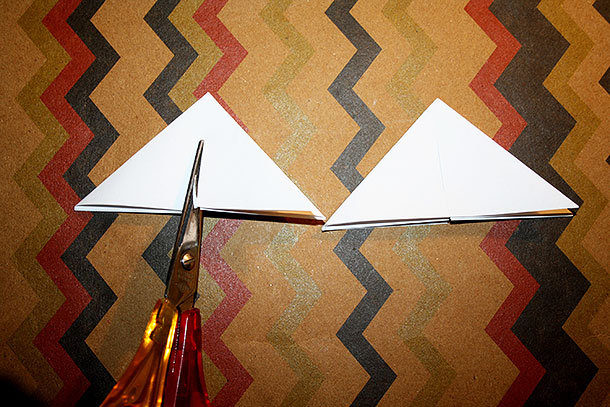 Das entstandene Dreieck wird an der langen Seite bis zur Mitte eingeschnitten.